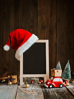 Christmas decoration with blank signboard and santa claus hat