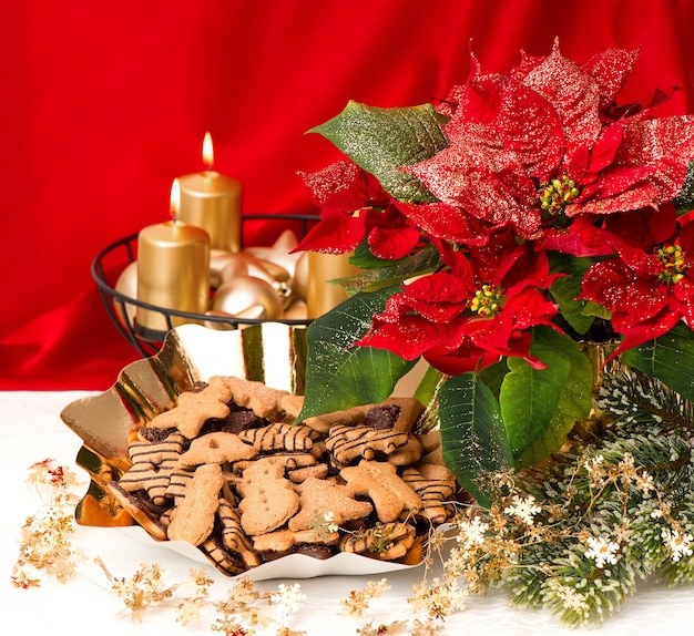 Christmas decoration with burning golden candles, poinsettia flower and christmas cookies