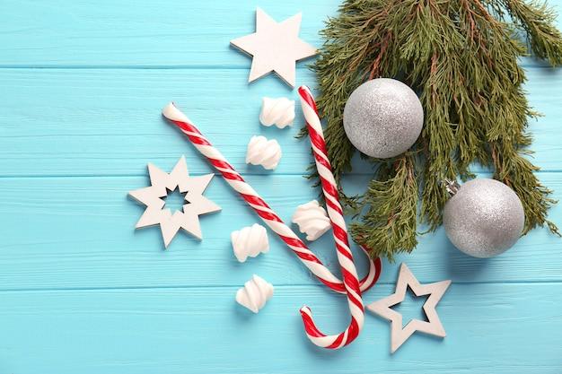青い木製のテーブルにキャンディケインとクリスマスの装飾