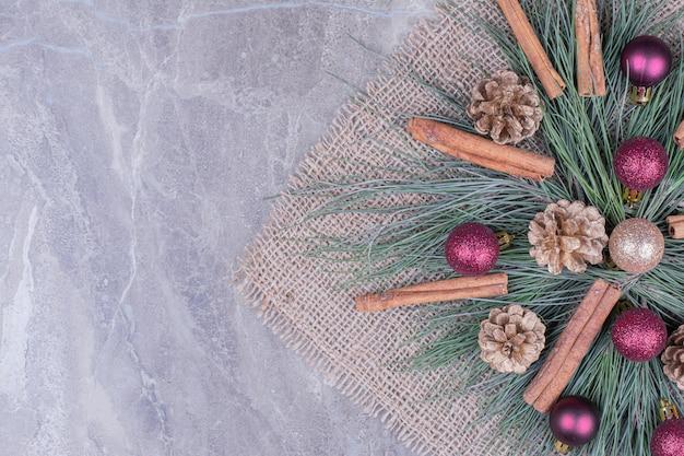 Decorazione natalizia con cinnamons, coni e rami di quercia