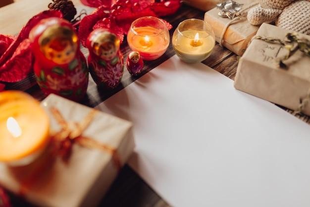 クラフトペーパー、ギフトボックス、手作りのクリスマスおもちゃ、キャンドルを使ったクリスマスデコレーション。木製の机の上面図。