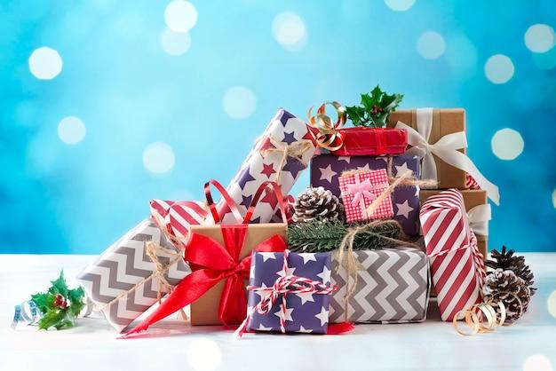 青い背景にお祝いのギフトボックスとリボンでクリスマスの装飾。休日のクリスマスのコンセプト。