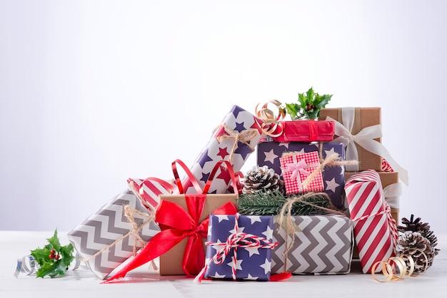 明るい背景にお祝いのギフトボックスとリボンでクリスマスの装飾。休日のクリスマスのコンセプト。
