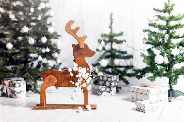 Christmas decoration with gift boxes, moose or reindeer and christmas trees on snow. presents under the fur-trees, christmas, selective focus.