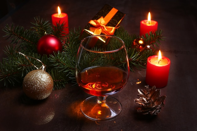 Christmas decoration with glass of cognac or whiskey, red candles, gift box and christmas tree.