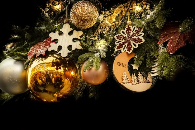 Christmas decoration with golden balls and wooden snowflakes and fir branches on black background. merry christmas and happy new year postcard backdrop