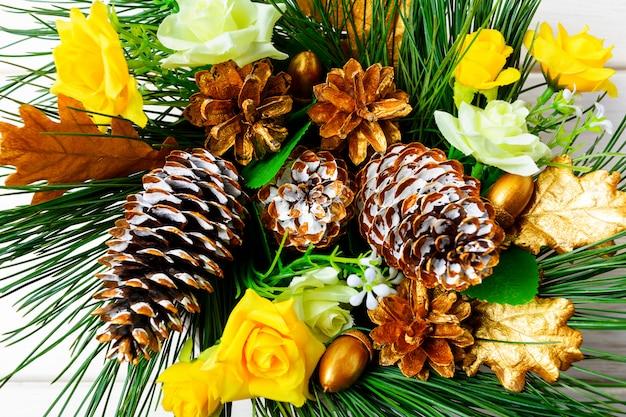 Новогоднее украшение с золотыми украшенными сосновыми шишками и шелковыми розами