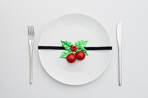 Christmas decoration with holly leaves and red balls on white plate