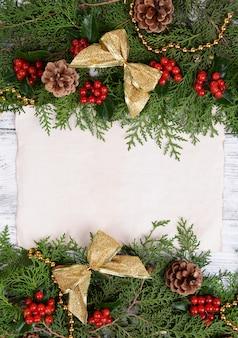 木製の背景に紙シートとクリスマスの装飾