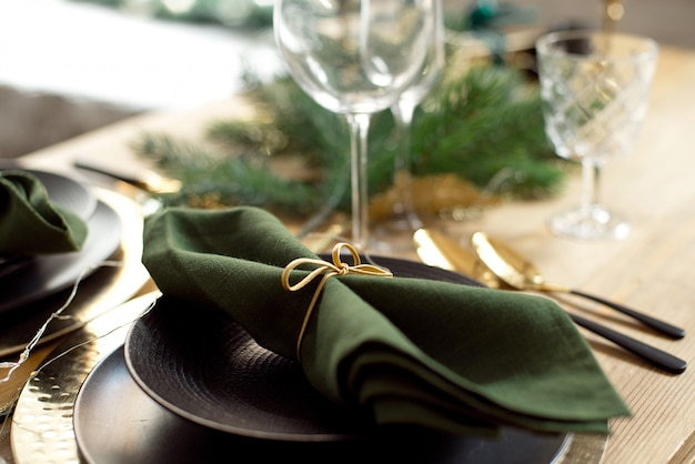 Christmas decoration with pine branches, table setting and candles on a dark christmas tree background