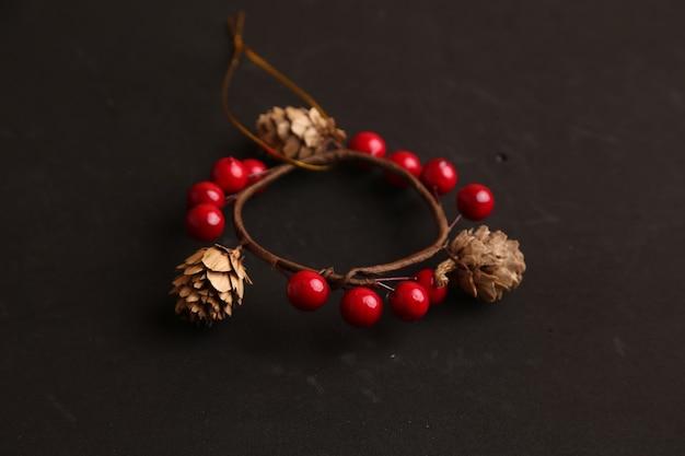 Decorazione natalizia con pigne e palla rossa isolata sul nero