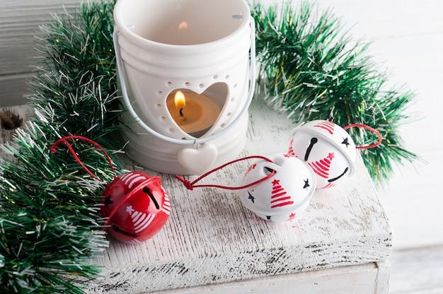 Новогоднее украшение с красными и белыми колокольчиками и свечой на белом деревенском фоне