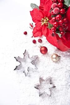빨간 양 초, 열매, 포 인 세 티아 꽃과 쿠키 커터 눈송이 모양의 크리스마스 장식. 휴일 크리스마스와 새 해 개념입니다.