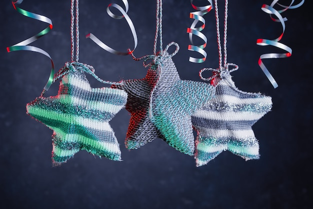 Christmas decoration with silver knitted stars and silver confetti ribbons.