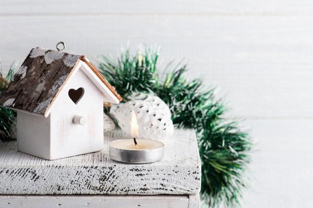 Новогоднее украшение с игрушечным деревянным скворечником и зажженной свечой на белом деревенском фоне. скопируйте место для приветствия