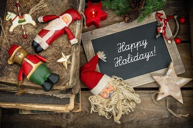 木製の背景にヴィンテージのつまらないものやおもちゃでクリスマスの装飾。ノスタルジックなレトロ風の写真。ダークデザインのセレクティブフォーカス