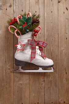 Christmas decoration with vintage skate on wooden wall