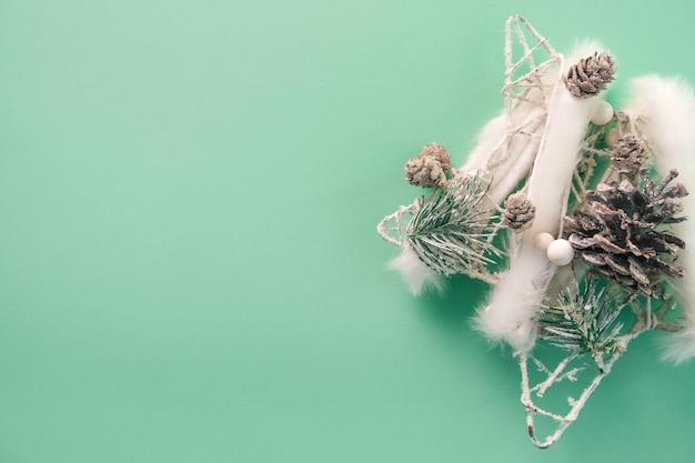Christmas decoration with white fur, beads and cones on a beautiful mint background.