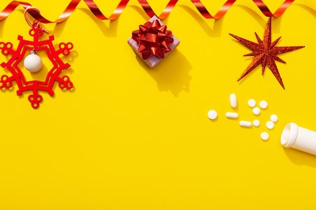 Новогоднее украшение с белыми таблетками как символ празднования с инфекцией и лечением