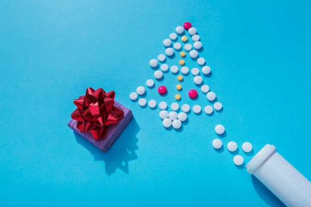 Christmas decoration with white pills and bottle as a symbol of celebrating with covid19 infection