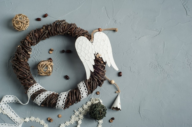 Christmas decoration with wicker ring, laces, angel wings