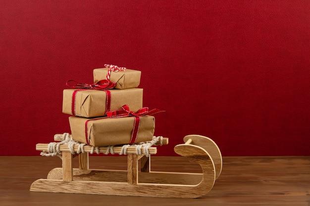 Новогоднее украшение с деревянными санями, сосны, подарки с копией пространства на красном фоне