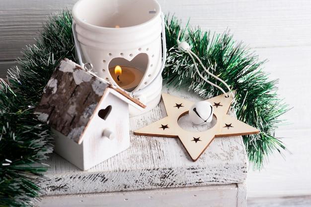 Новогоднее украшение с деревянной звездой и зажженной свечой на белом деревенском фоне. скопируйте место для приветствия