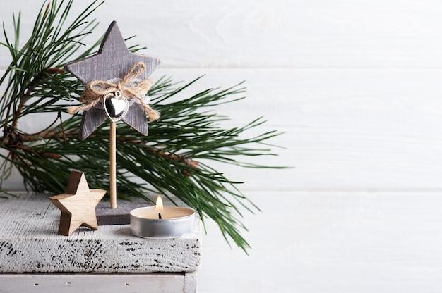 Новогоднее украшение с деревянными звездами и зажженной свечой на белом деревенском фоне. скопируйте место для приветствия