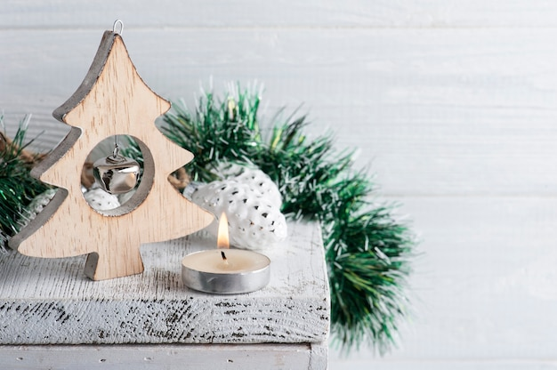 Новогоднее украшение с деревянными звездами и зажженной свечой на белой деревенской поверхности. скопируйте место для приветствия