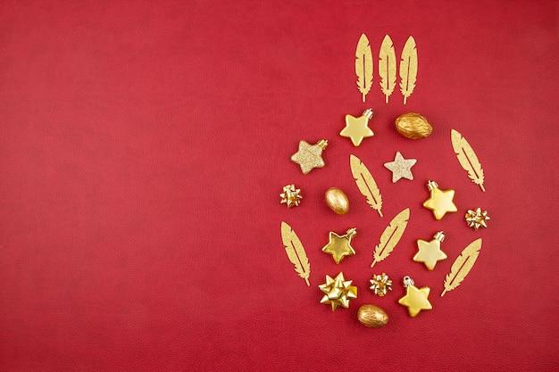 赤い背景の上のコピースペースでクリスマスゴールデン飾りとクリスマスの装飾