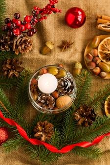 休日の家やテーブルを飾るためにあなた自身の手でクリスマスの装飾。ガラスの花瓶のキャンドル、ナッツ、コーン、ドングリ。上面図。