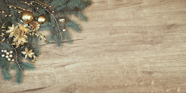 Christmas decoration on wood with a corner of decorated fir tree branches, copy-space