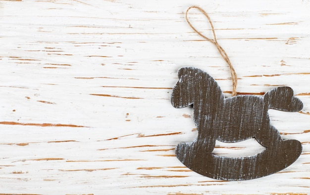 Christmas decoration-a wooden horse on an old white table. new year.