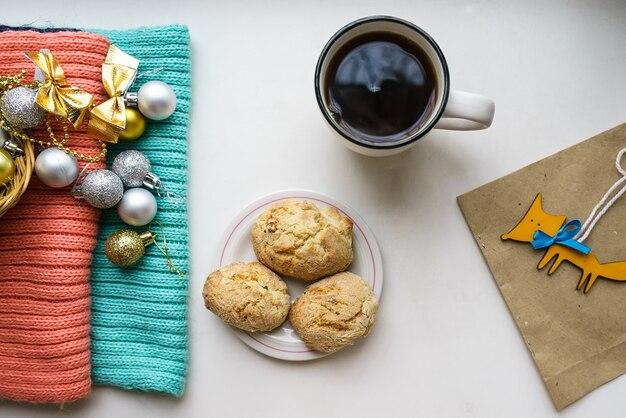 Елочные игрушки, чашка чая и домашнее печенье на подоконнике