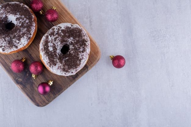 Рождественские украшения и пончики на деревянной доске на белом фоне.