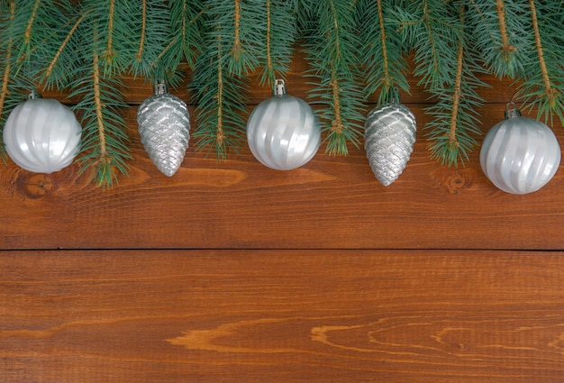 クリスマスの飾りとモミの枝は、テキスト用のスペースがある暗い木製の背景に平らに横たわっています。