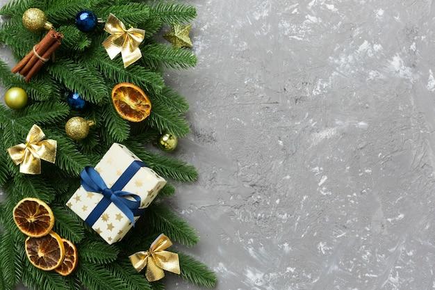 クリスマスの飾りとモミの木の枝と暗いテーブルのギフトボックス。コピースペースのあるトップビューフレーム