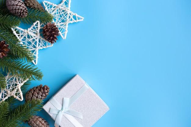 青い背景に、クリスマスの飾りとギフトボックス。新年のコンセプト。