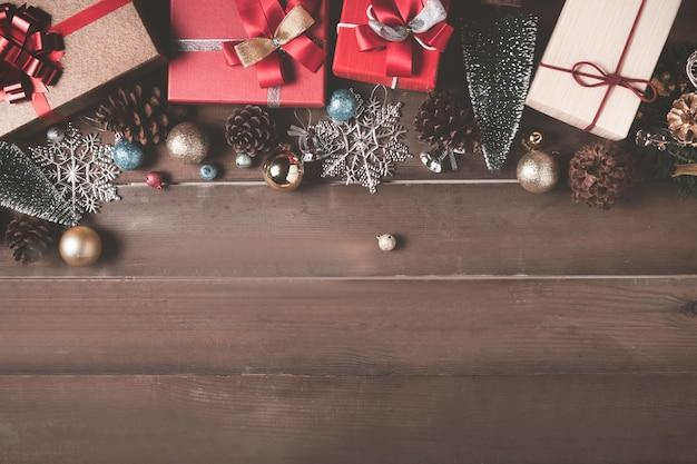 木の背景にクリスマスの装飾やギフトボックス。フラットレイ、上面図