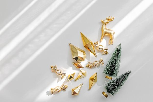 テキスト用の空のコピースペースと白い背景の上の金色のクリスマスの装飾とギフト。休日のコンセプト。フラットレイ、上面図