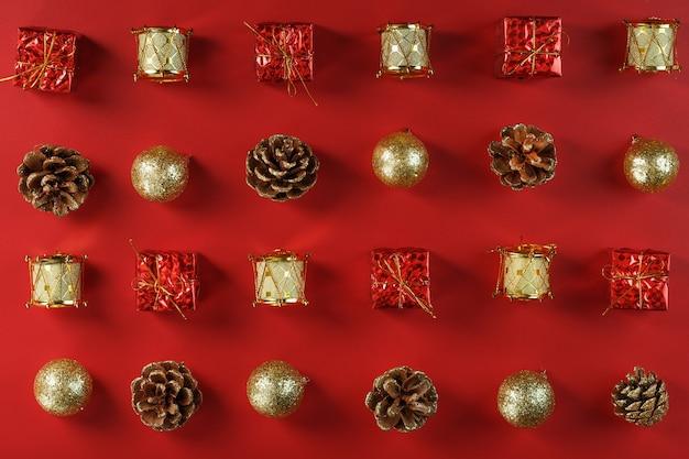 赤い背景の上の行とパターンのクリスマスの装飾とギフト