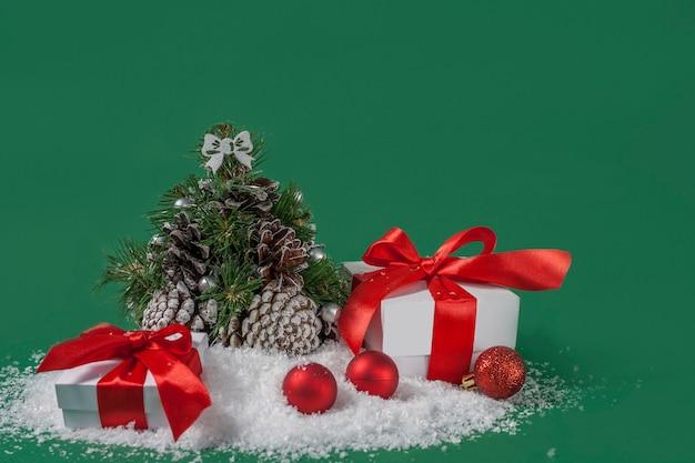 コピースペースと緑の背景に雪の上のクリスマスの装飾やギフト。
