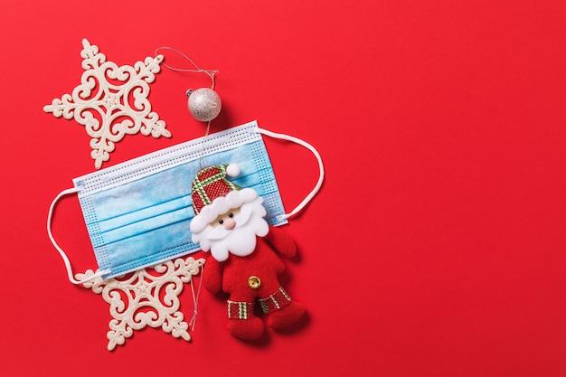 코로나바이러스로 인해 휴일 동안 격리 주제에 대한 복사 공간 개념이 있는 빨간색 배경에 크리스마스 장식 및 의료 마스크