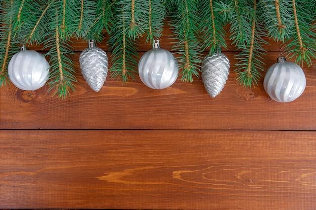 크리스마스 장식과 소나무 바늘은 상단에서 텍스트 사진을위한 공간이있는 어두운 나무 배경에 평평하게 놓여 있습니다.