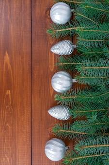 クリスマスの飾りと松葉は、テキスト用のスペースのある暗い木製の背景に平らに置かれました。