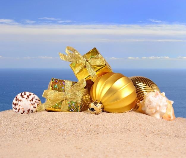 Рождественские украшения и ракушки на песчаном пляже на фоне моря