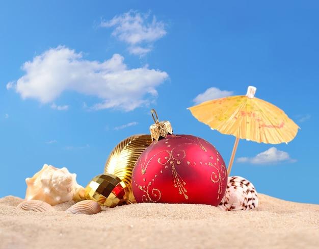 Рождественские украшения и ракушки на песчаном пляже на фоне голубого неба