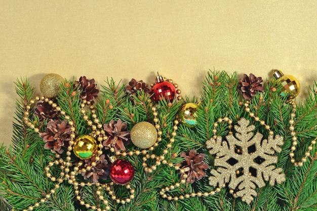 金色の背景にクリスマスの装飾とトウヒの枝と円錐形