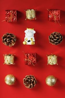 赤い背景の上の牛とクリスマスの装飾やおもちゃ