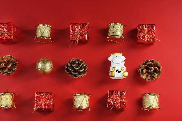 크리스마스 장식과 빨간 벽에 암소와 장난감. 황소는 새로운 2021 년의 상징입니다.